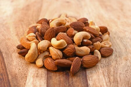Mixed salted nuts on wood cutting board Stok Fotoğraf