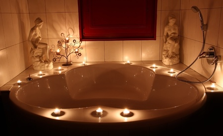 Romantic bathtub with lit candles Editorial
