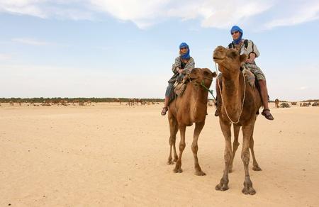 Pareja joven en camello en el desierto