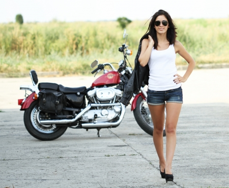 Young beautiful woman walking from a motorcycle photo