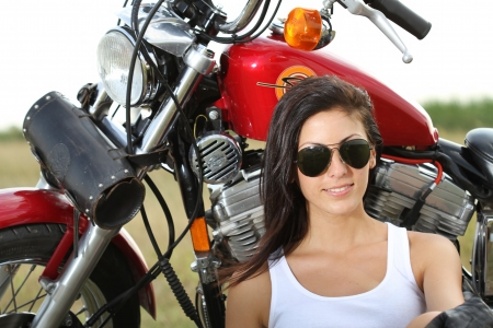 Beautiful young woman standing near a motorcycle photo