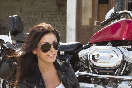 woman motorcycle: Beautiful girl rider near a motorcycle Stock Photo