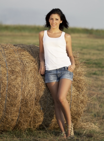 country girl: Cute country girl near a bale of straw