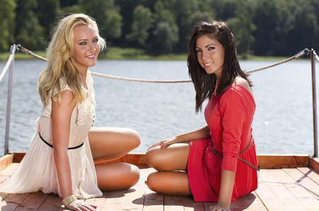long lake: Beautiful young women on a lake pontoon