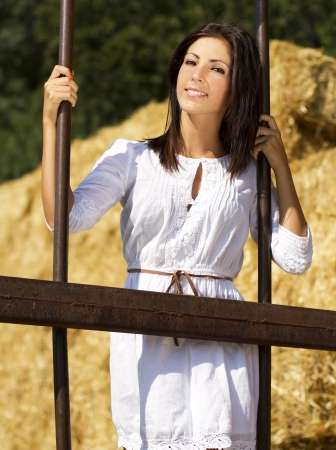 Young country girl near behind old iron bars Stock Photo - 14855120