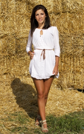 Cute country girl near a straw bales wall photo