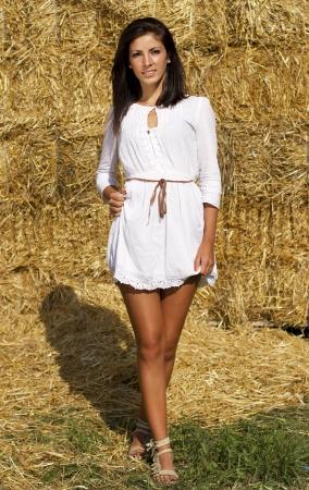 belles jambes: Fille mignonne de pays près de paille balles un mur
