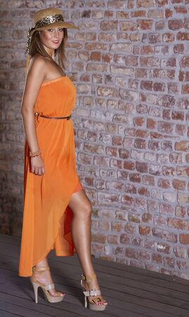 area sexy: Attractive young woman in orange long dress