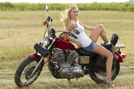woman motorcycle: Sexy blond girl standing on a motorcycle