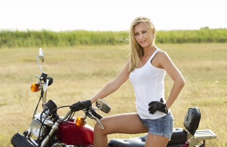Beautiful blond woman on a motorcycle photo