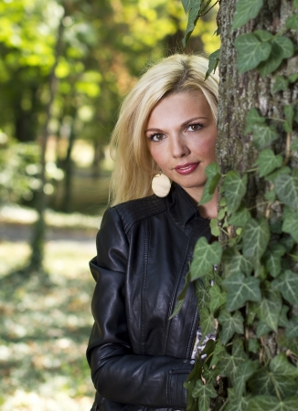 Beautiful blond woman hiding behind a tree