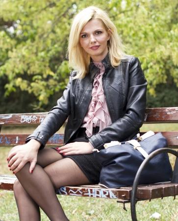 belles jambes: Bonne femme regardant debout sur un banc dans un parc Banque d'images