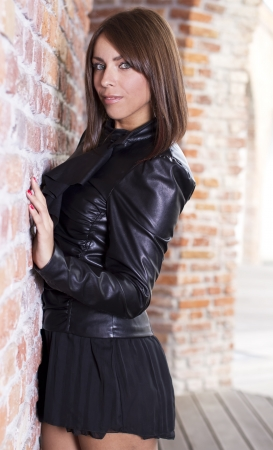Beautiful brunette girl near a retro brick wall photo