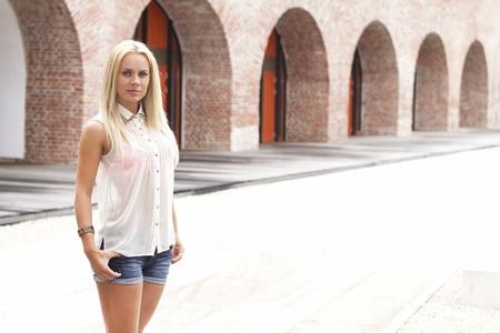 rubia ojos azules: Mujer joven cerca de un edificio de época Foto de archivo