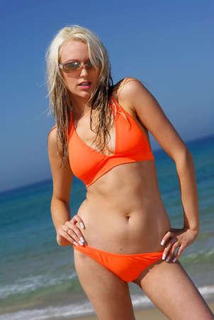 Beautiful Girl en la playa usando bikini naranja.  Foto de archivo - 2995681