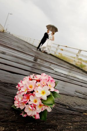 Wedding flowers on board walk with wedding couple in background