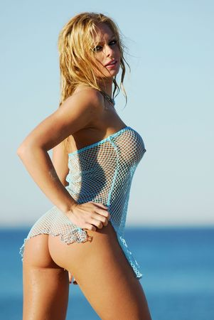 erotic fantasy: Beautiful girl on beach wearing blue fishnet top.