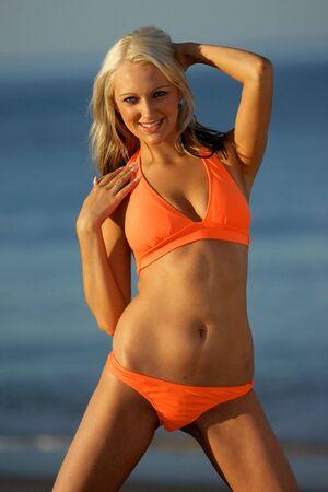 Beautiful Girl on beach wearing orange bikini. Stock Photo - 3047851