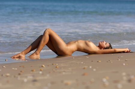 tetas: Mujer desnuda posando en la playa