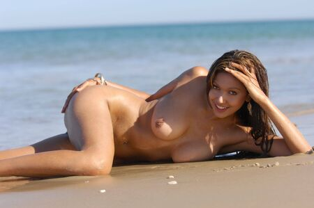 Naked woman posing on beach Stock Photo