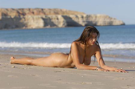 tieten: Naakte vrouw die zich op het strand