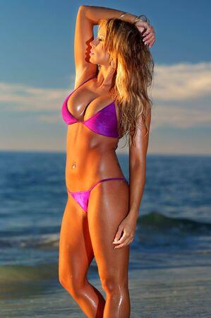 Beautiful bikini girl on beach at sunset  photo