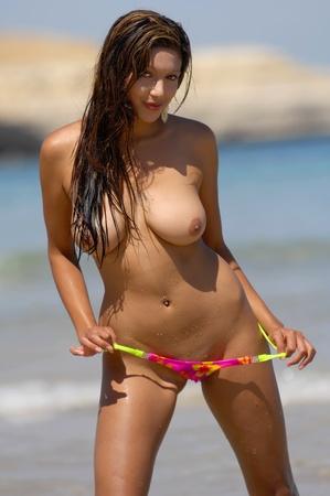 tetas: Mujer sexy topless posando en la playa