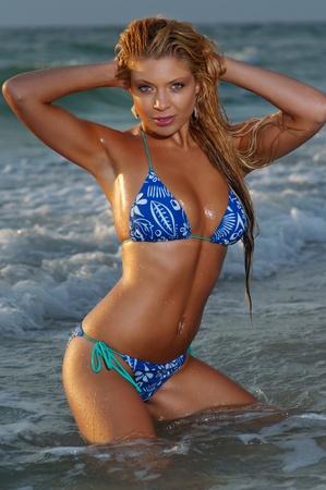 Beautiful blonde bikini girl posing on beach.