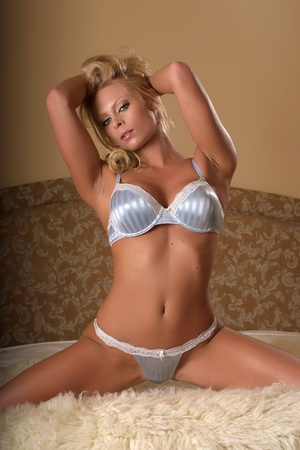Sexy woman posing on bed in blue lingerie
