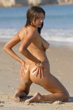 erotic fantasy: Beautiful naked woman posing on beach  Stock Photo