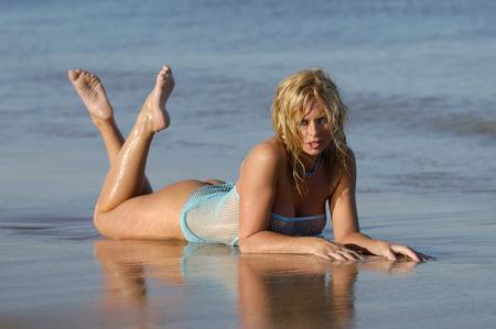 Sexy blonde woman posing on beach wearing blue fishnet top  photo