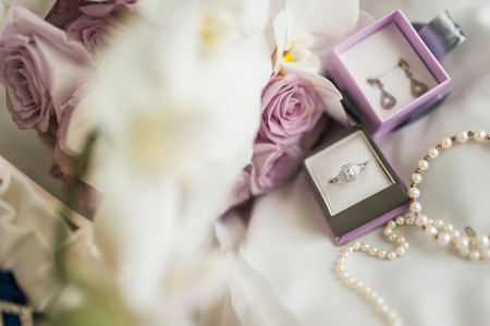 Close up photo of bridal jewelry and flowers