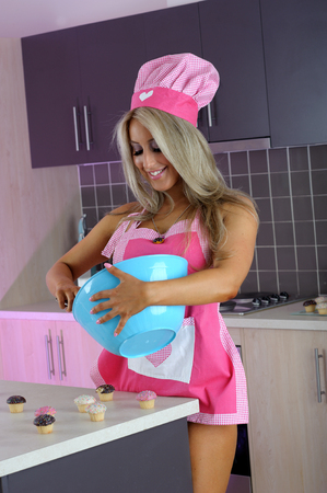 Sexy blonde pastry chef in kitchen