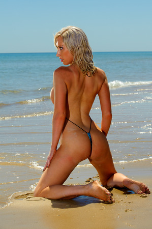 Sexy beach  girl wearing micro bikini photo