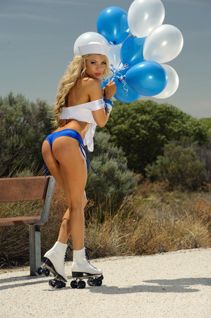 Sexy blonde girl on rollerskates and balloons