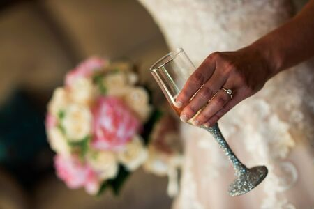 Bride wearing ring holding champagne glass and bouquet
