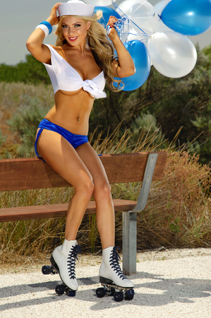 Sexy blonde girl on rollerskates with balloons