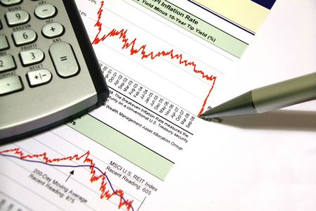 Financial calculator on a printed sheet with financial charts and a pen remarking the last market slump photo