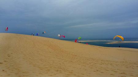 Paragliding on the beach at Dune du Pilat, France Atlantic Ocean - colourful paraglider 免版税图像