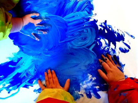closeup of children hands painting during a school activity - learning by doing, education and art, art therapy concept.