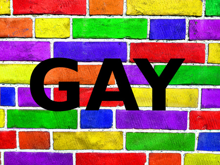 Rainbow flag on a brick wall, old brick wall texture background, gay pride, free love, human rights concept. Writing GAY. Stockfoto