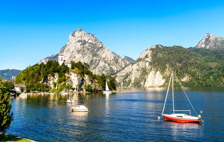 Traunkirchen im Salzkammergut, Austria. Nearby Salzburg, Gmunden. Beautiful colorful Postcard view with a Church Maria Kronung, alps mountains, Traunstein mountain,  boats, sailboats blue sky