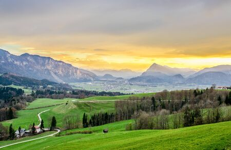 Beautiful sunset panorama view in Inntal on alps in Tirol, Austria. With green fields near Kufstein, Kaiser, Kaisergebirge, border with Bavaria (Bayern) Germany.