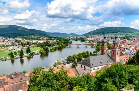 beautiful postcard View from castle on old german town Miltenberg am Main river, St. Jacob catholic church, main bridge.     Odenwald, Bavaria, Germany Редакционное