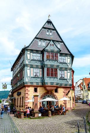 8 August 2019: Oldest Hotel from1158  (alteste Gasthaus Deutschlands), half-timbered houses, restaurant, shops, peaple in old german town Miltenberg am Main river. Odenwald, Bavaria, Germany