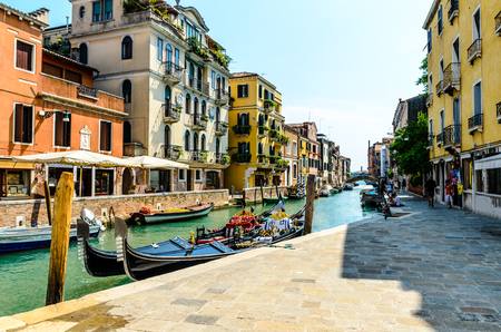 Beautiful view on canal with gongola, gondolas, colorful houses, restaurants in Venice, Italy.