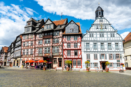1 August 2019: Market place, square (Marketplace, Marktplatz) with half-timbered colorful houses, town hall (Rathaus), peaple in old town Butzbach, Hessen, Germany