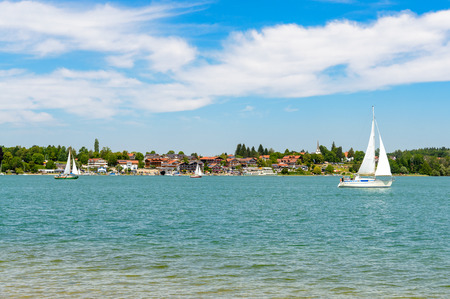 View on lake Chiemsee with a boat, Sailboat on Gstadt from Fraueninsel, Frauenchiemsee.  Bavaria, Bayern, Germany