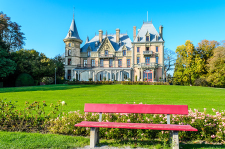 Thun, Switzerland - Oktober 28 2014: Schadau Castle on Thun Lake (Thunersee, Thuner See), red, pink bench