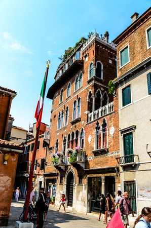11 July 2013: Beautiful red orange house with italian flag in Venice, Italy Editorial